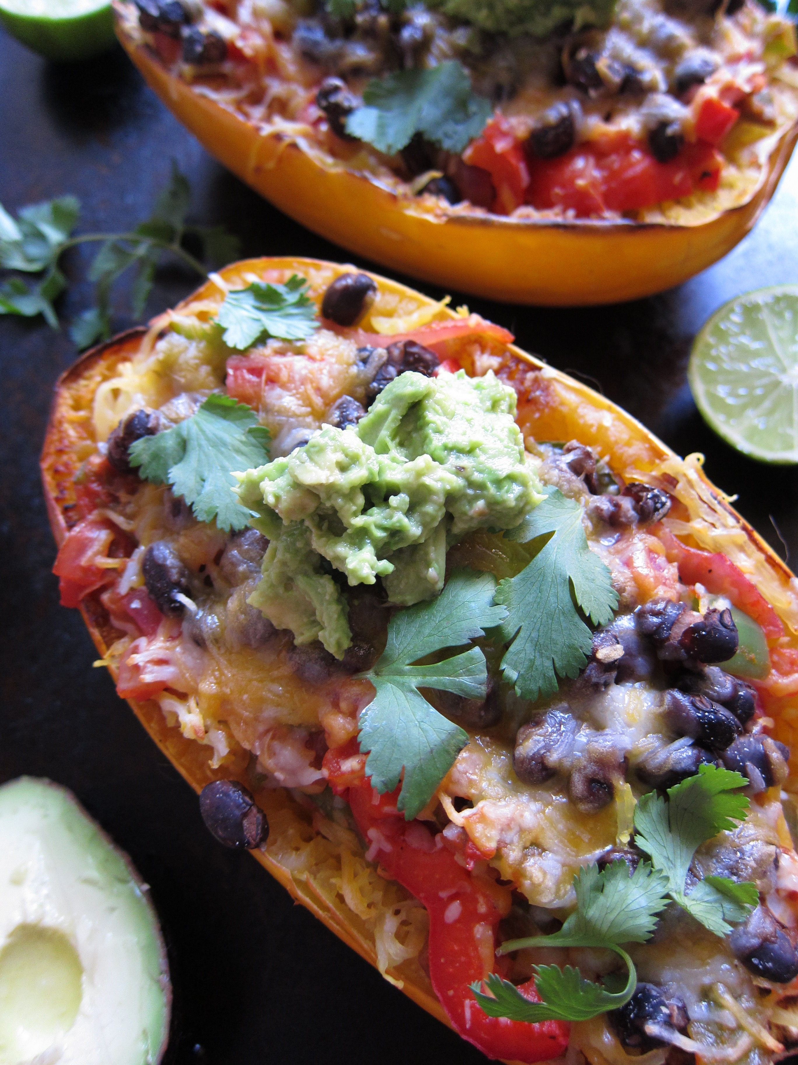 Spaghetti Squash Burrito Bowl is a meatless meal your family will love. This hearty and good-for-you meal is full of green and red peppers, onions and black beans and topped with plenty of cheese and a scoop of guacamole.